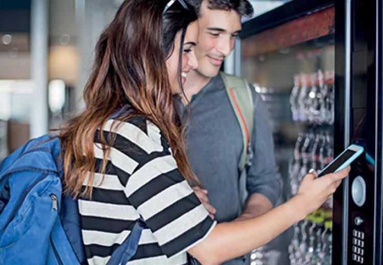 couple with phone at vending machine